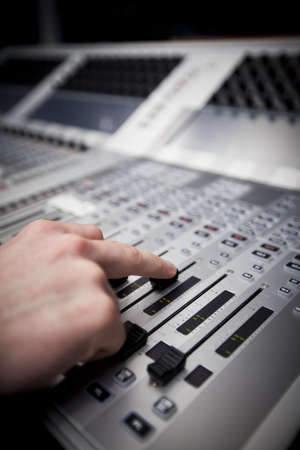 dubbing: Close-up of a hand on a fader on a television studio sound desk.