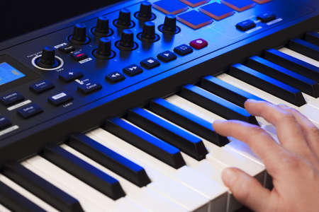 keyboard instrument: Close up of a hand playing a MIDI controller keyboard.