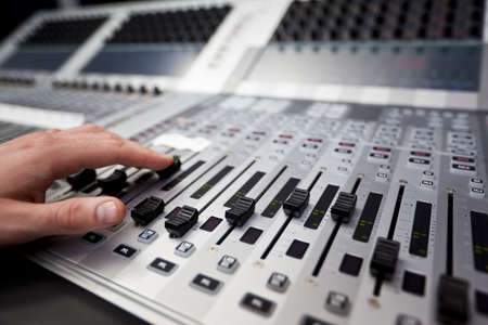are sound: Primer plano de una mano sobre un fader en un escritorio estudio de televisi�n de mezcla.