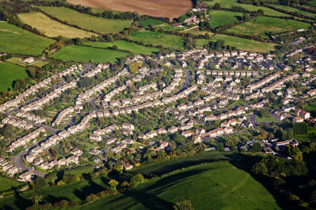 Aerial view of an English housing estate surrounded by green fields.