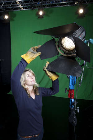 Female lighting engineer adjusts the barn doors on a light inside a Television Studio.