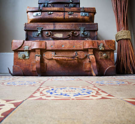 Stack of old leather luggage on tiled floor, copy space on floor