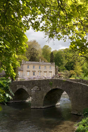 Georgian Manor house, framed by trees in a rural setting beside a stone bridge and river  Stock Photo