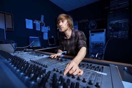 geluid: Man met behulp van een sound mixing desk in een opnamestudio