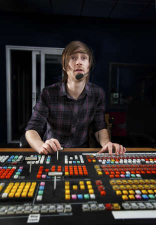 Man sat at a Vision Mixing panel in a Television Studio Gallery