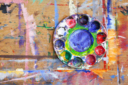 splashed: Close-up of a multi-coloured plastic paint palette on a paint splashed wooden board