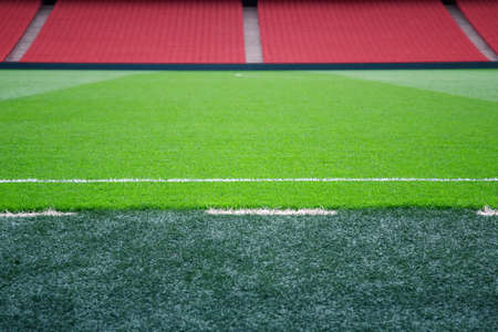 touchline: Empty football pitch with red seating, selective focus on touchline