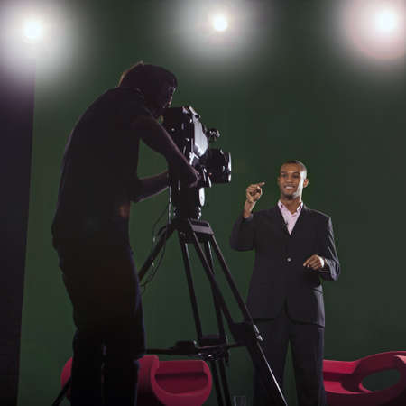 Presenter talks to camera with silhouette of cameraman in foreground and studio lights in the background  Stock Photo
