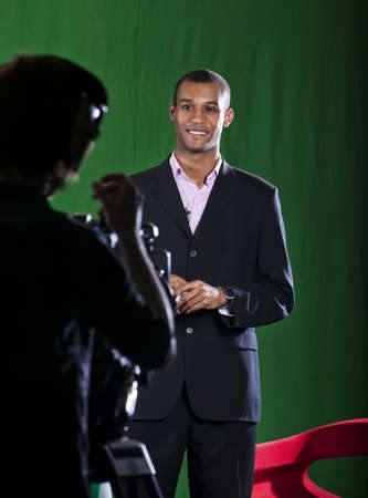 Presenter in a green screen Television studio chats with a camera operator silhouetted in foreground