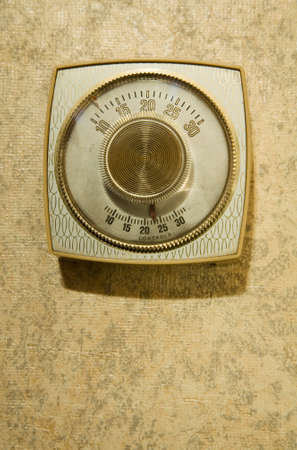 old fashioned gold and cream thermostat and wallpaper