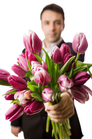 three people only: A man holds out a bunch of tulips, narrow depth of field with focus on front tulips  Stock Photo
