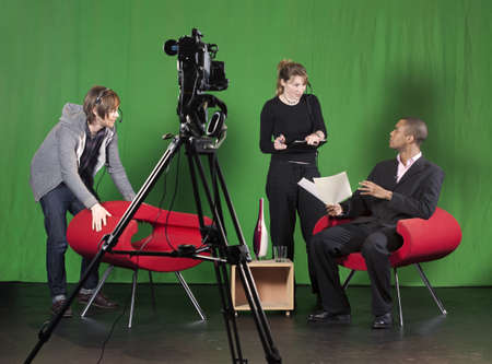 A crew member arranges furniture whilst the floor manager talks to the presenter on a TV studio set  TV camera on a tripod out-of-focus in the foreground  Stock Photo