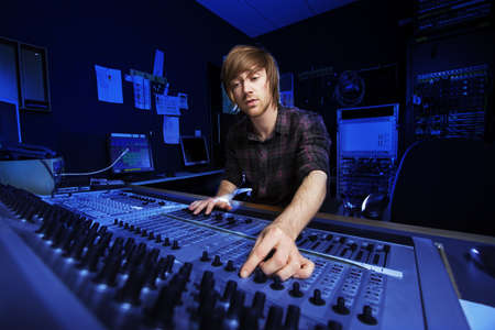 dubbing: Man using a sound mixing desk in a recording studio