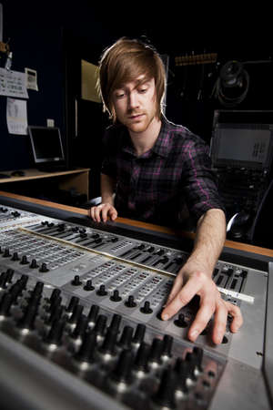 dubbing: Sound engineer using a studio mixing desk  Selective focus on Sound desk  Stock Photo