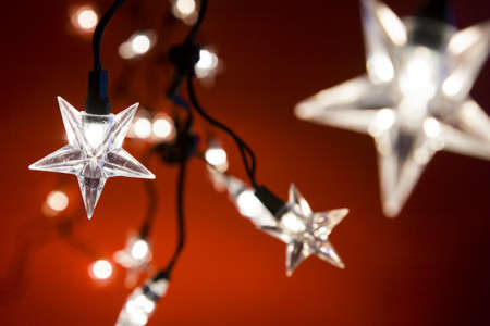 star shaped: Line of star shaped Christmas lights against a red background, narrow depth of field
