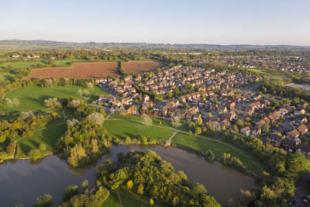 Aerial view of an English Surburban town next to a river and fields