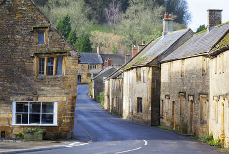 Old stone buildings on the high street of  a traditional english Village