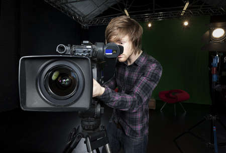 Operator looks into the viewfinder of a television studio camera, with lights and CSO green curtain in the background