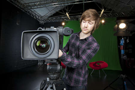 Young man preparing a Television studio camera, with studio lights and CSO green curtain in the background