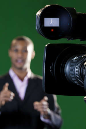 Close-up of a television camera viewfinder and lens with a presenter out of focus in the background  Viewfinder display added in post-production  Stock Photo