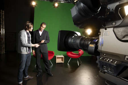film camera: Foreground Television camera with floor manager and presenter out-of-focus in the background