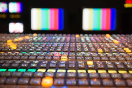 Television gallery with selective focus on the foreground vision mixing panel and TV monitors out of focus in the background  Stock Photo