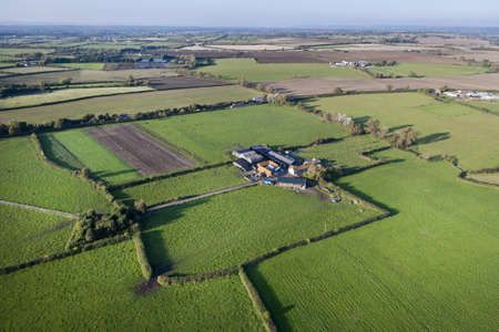 Aerial view of a farm set amongst agricultural land in Somerset, UK