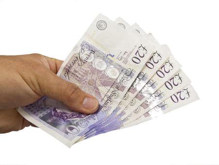 sterlina: Primo piano di una mano di £ 100 a venti note su uno sfondo bianco