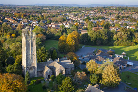 Aerial view of an English village featuring old church, small school and modern houses set in the British countryside  photo