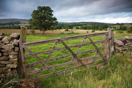 english countryside: Rustic gate in drystone wall in Cumbria, England, UK  Stock Photo