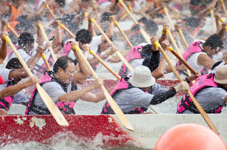 Teams of men in Dragon boats paddle vigorously in a  race in the downtown area of Singapore on 21st November 2004  Dragon Boat Racing is a popular team sport in Singapore