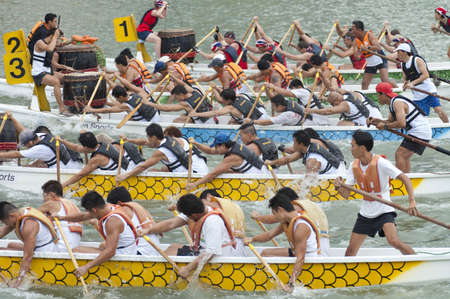 Teams compete in a dragon boat race in Singapore on 21st November 2004  Steersmen stand at the back of each boat, while drummers drive the paddlers rhythm from the front
