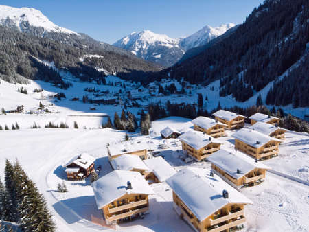chalets: Gargellen, a village in the Austrian Alps, with snow covered chalets in the foreground and mountains in the background  Stock Photo