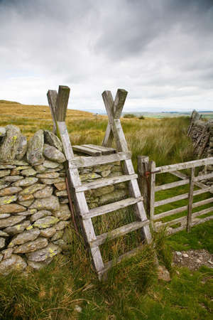 dry stone: Old wooden ladder stile set against the beautiful Cumbrian countryside  Stock Photo