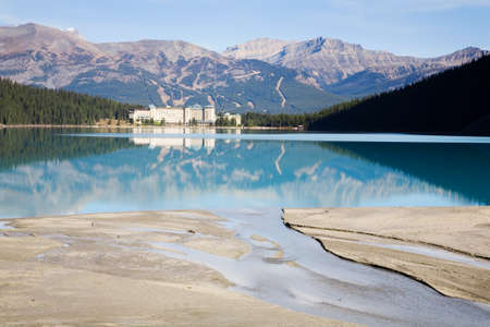 banff: blue tinged waters of lake louise reflect the chateau hotel with foreground silt streams that feed the lake and background showing the many snowless ski slopes