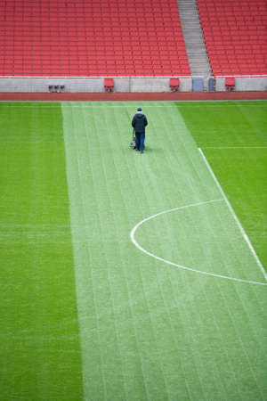 mowing grass: lone groundsman cuts the grass on a large football pitch
