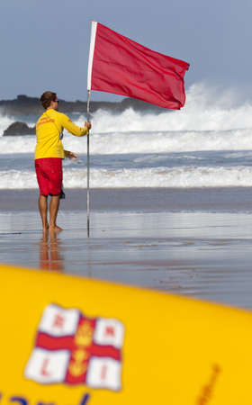 warns: ST IVES, UK - September 11   A lifeguard from the Royal National Lifeboat Institution on Porthmeor beach in St Ives, Cornwall on 11th September 2011  The flag warns swimmers not to enter the water