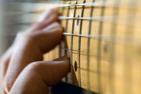 close-up of electric guitar fretboard with hand sliding a chord up the neck