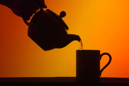 silhouette of teapot pouring a cup of tea into a mug against a tea coloured background