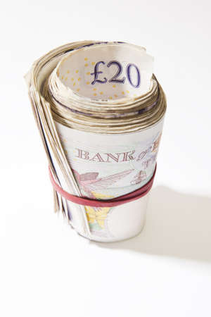 elastic band: A roll of British notes held together by an elastic band with a plain background
