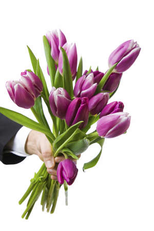 Close up of man holding out a bunch of flowers, isolated against white  photo