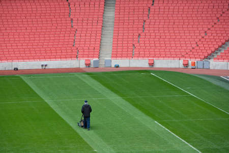 playing field: lone man cuts the turf at a large, empty football stadium  Editorial