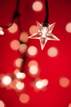 red christmas lights: Star shaped Christmas tree lights against red with very shallow depth of field