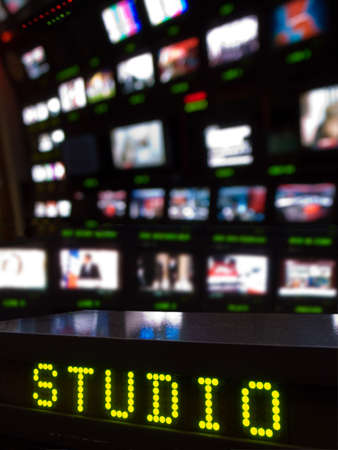 Television Gallery and foreground LED display with the word  Studio  and a bank of TV screens out of focus in the background