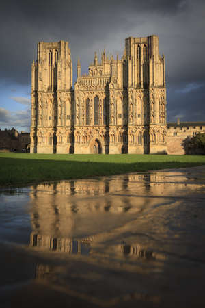 wells: The West Front of Wells Cathedral with foreground reflections in the wet paving stones