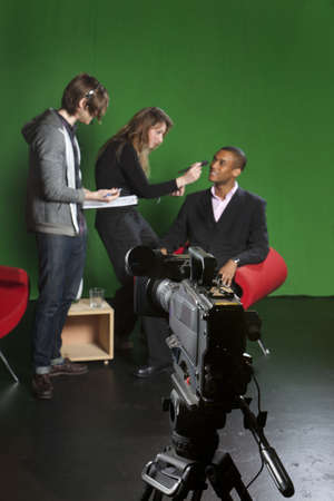 Selective focus on a studio television camera with a floor manager, make-up artist and presenter out of focus in the background  photo