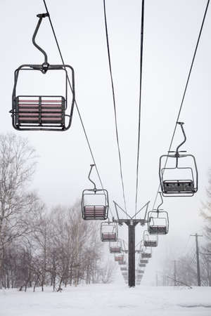 Empty chair lift in the mist and snow at Niseko ski resort in Japan  Shallow depth of field