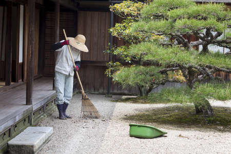 feudal: A gardener rakes the gravel in Ritsurin garden, Takamatsu, Japan on 8th May 2012  Ritsurin is a landscape garden built by the local feudal lords during the early Edo Period