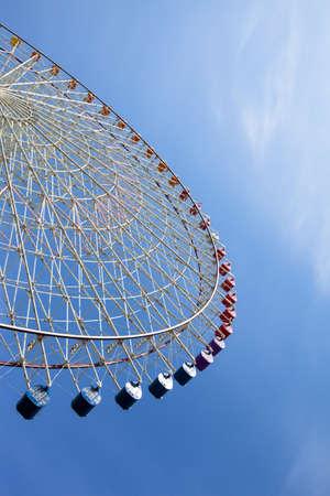 semicircular: Semi-circular section of a large ferris wheel against a sunny blue sky