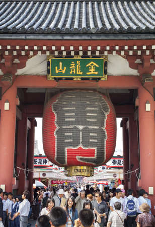 People walk under the lantern that hangs inside the Kaminarimon or Thunder Gate in the district of Asakusa in Japan